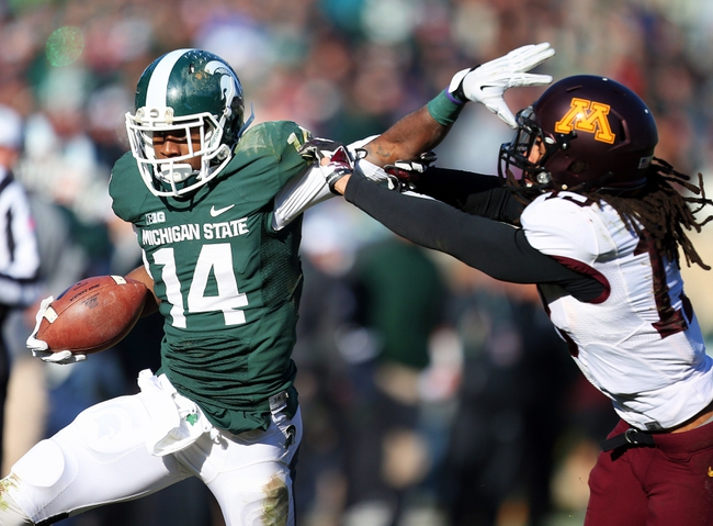 Nov 30, 2013; East Lansing, MI, USA; Michigan State Spartans wide receiver Tony Lippett (14) stiff arms Minnesota Golden Gophers defensive back Derrick Wells (13) during the 2nd half a game at Spartan Stadium.MSU won 14-3.  Mandatory Credit: Mike Carter-USA TODAY Sports