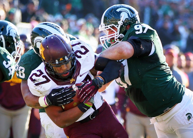 Nov 30, 2013; East Lansing, MI, USA; Minnesota Golden Gophers running back David Cobb (27) is tacked by Michigan State Spartans linebacker Denicos Allen (28) and defensive lineman Mark Scarpinato (97) during the 2nd half a game at Spartan Stadium.MSU won 14-3.  Mandatory Credit: Mike Carter-USA TODAY Sports