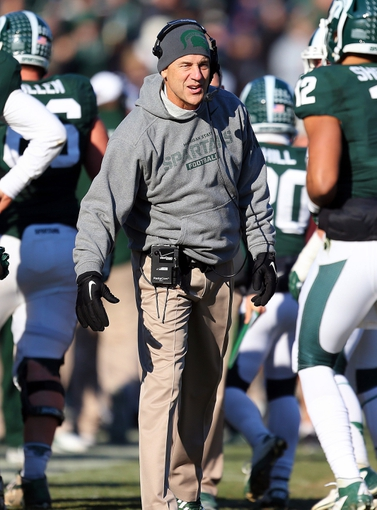 Nov 30, 2013; East Lansing, MI, USA; Michigan State Spartans head coach Mark Dantonio celebrates with players during the 2nd half against the Minnesota Golden Golphers at Spartan Stadium.MSU won 14-3.  Mandatory Credit: Mike Carter-USA TODAY Sports