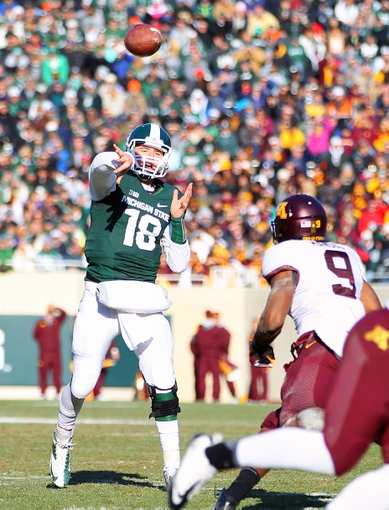 Nov 30, 2013; East Lansing, MI, USA; Michigan State Spartans quarterback Connor Cook (18) throws the ball to tight end Josiah Price (not pictured) for a touchdown during the 2nd half against the Minnesota Golden Golphers at Spartan Stadium.MSU won 14-3.  Mandatory Credit: Mike Carter-USA TODAY Sports