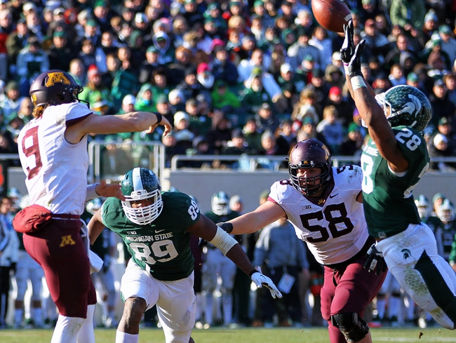 Nov 30, 2013; East Lansing, MI, USA; Minnesota Golden Gophers quarterback Philip Nelson (9) throws the ball against Michigan State Spartans defensive end Shilique Calhoun (89) and linebacker Denicos Allen (28) during the 2nd half a game at Spartan Stadium.MSU won 14-3.  Mandatory Credit: Mike Carter-USA TODAY Sports
