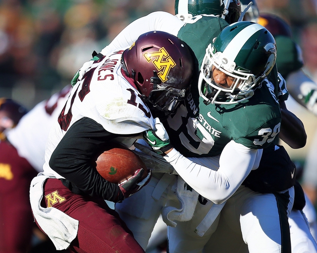 Nov 30, 2013; East Lansing, MI, USA; Minnesota Golden Gophers quarterback Conor Rhoda (15) is sacked by Michigan State Spartans cornerback Jermaine Edmondson (39) during the 2nd half a game at Spartan Stadium.MSU won 14-3.  Mandatory Credit: Mike Carter-USA TODAY Sports