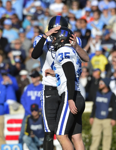 Nov 30, 2013; Chapel Hill, NC, USA;  Duke Blue Devils kicker Ross Martin (35) celebrates with holder Will Monday (41) after kicking the game winning field goal in the fourth quarter. The Duke Blue Devils defeated the North Carolina Tar Heels 27-25 at Kenan Memorial Stadium. Mandatory Credit: Bob Donnan-USA TODAY Sports