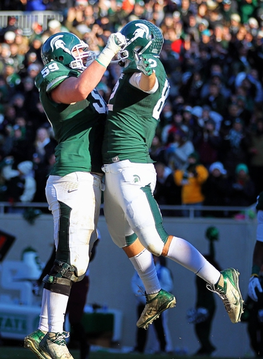 Nov 30, 2013; East Lansing, MI, USA; Michigan State Spartans tight end Josiah Price (82) and offensive linesman Dan France (59) celebrate a touchdown during the 2nd half against the Minnesota Golden Golphers at Spartan Stadium.MSU won 14-3.  Mandatory Credit: Mike Carter-USA TODAY Sports