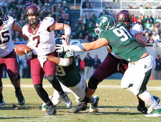 Nov 30, 2013; East Lansing, MI, USA; Minnesota Golden Gophers quarterback Mitch Leidner (7) has ball stripped by Michigan State Spartans defensive end Shilique Calhoun (89) during the 2nd half a game at Spartan Stadium.MSU won 14-3.  Mandatory Credit: Mike Carter-USA TODAY Sports