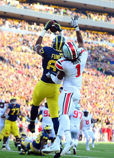 Nov 30, 2013; Ann Arbor, MI, USA; Michigan Wolverines tight end Devin Funchess (87) catches a pass in the end zone for a touchdown while being defended by Ohio State Buckeyes cornerback Bradley Roby (1) during the fourth quarter at Michigan Stadium. Mandatory Credit: Andrew Weber-USA TODAY Sports