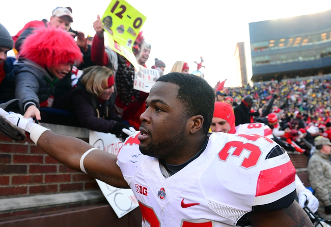 Nov 30, 2013; Ann Arbor, MI, USA; Ohio State Buckeyes running back Carlos Hyde (34) celebrates with fans after defeating Michigan Wolverines 42-41 at Michigan Stadium. Mandatory Credit: Andrew Weber-USA TODAY Sports