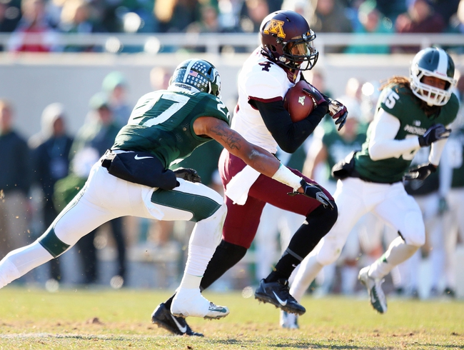 Nov 30, 2013; East Lansing, MI, USA; Minnesota Golden Gophers quarterback Donovahn Jones (4)  runs the ball against Michigan State Spartans safety Kurtis Drummond (27) during the 2nd half a game at Spartan Stadium.MSU won 14-3.  Mandatory Credit: Mike Carter-USA TODAY Sports