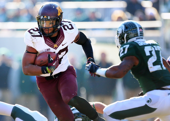 Nov 30, 2013; East Lansing, MI, USA; Minnesota Golden Gophers running back David Cobb (27) runs the ball against Michigan State Spartans safety Kurtis Drummond (27) during the 2nd half a game at Spartan Stadium.MSU won 14-3.  Mandatory Credit: Mike Carter-USA TODAY Sports