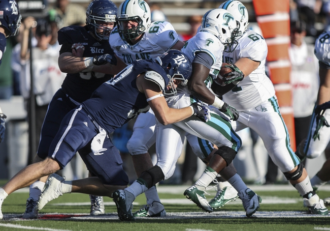 Nov 30, 2013; Houston, TX, USA; Tulane Green Wave running back Orleans Darkwa (26) runs with the ball as Rice Owls safety Gabe Baker (40) makes a tackle during the second quarter at Rice Stadium. Mandatory Credit: Troy Taormina-USA TODAY Sports