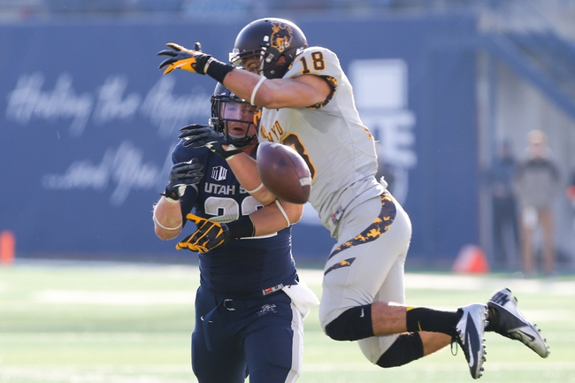 Nov 30, 2013; Logan, UT, USA; Utah State Aggies tight end Keegan Andersen (22) and Wyoming Cowboys safety Xavier Lewis (18) both attempt to catch the ball during the third quarter at Romney Stadium. Utah State Aggies won the game 35-7. Mandatory Credit: Chris Nicoll-USA TODAY Sports