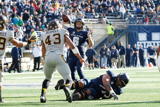 Nov 30, 2013; Logan, UT, USA; Utah State Aggies quarterback Darell Garretson (6) throws the ball over the Wyoming Cowboys defensive line during the third quarter at Romney Stadium. Utah State Aggies won the game 35-7. Mandatory Credit: Chris Nicoll-USA TODAY Sports