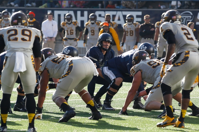 Nov 30, 2013; Logan, UT, USA; Utah State Aggies quarterback Darell Garretson (6) looks over Wyoming Cowboys defensive line at Romney Stadium. Utah State Aggies won the game 35-7. Mandatory Credit: Chris Nicoll-USA TODAY Sports