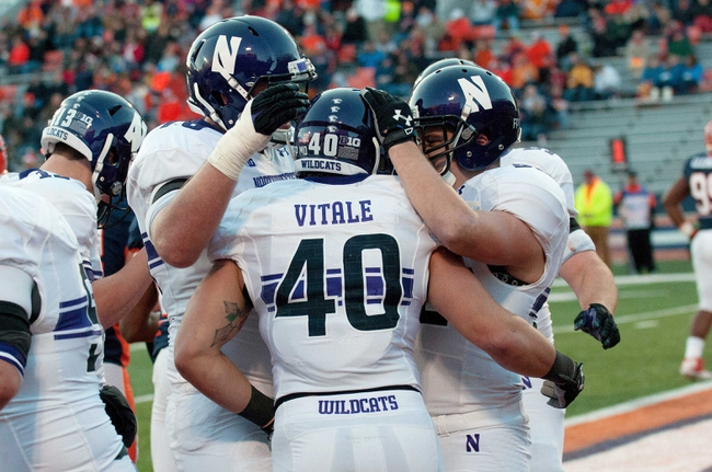Nov 30, 2013; Champaign, IL, USA;  Northwestern Wildcats fullback Dan Vitale (40) is congratulated by teammates after his touchdown during the second quarter against the Illinois Fighting Illini at Memorial Stadium. Mandatory Credit: Bradley Leeb-USA TODAY Sports