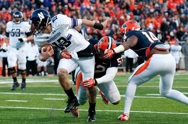 Nov 30, 2013; Champaign, IL, USA;  Northwestern Wildcats quarterback Trevor Siemian (13) is brought down by Illinois Fighting Illini linebacker T.J. Neal (52) during the second quarter at Memorial Stadium. Mandatory Credit: Bradley Leeb-USA TODAY Sports