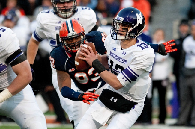 Nov 30, 2013; Champaign, IL, USA;  Northwestern Wildcats quarterback Trevor Siemian (13) runs from Illinois Fighting Illini defensive lineman Teko Powell (93) during the second quarter at Memorial Stadium. Mandatory Credit: Bradley Leeb-USA TODAY Sports