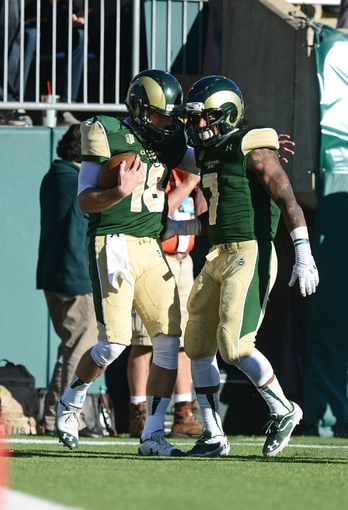 Nov 30, 2013; Fort Collins, CO, USA; Colorado State Rams quarterback Garrett Grayson (18) is congratulated after his rushing touchdown by running back Donnell Alexander (7) in the third quarter against the Air Force Falcons at Hughes Stadium. The Rams defeated the Falcons 58-13. Mandatory Credit: Ron Chenoy-USA TODAY Sports