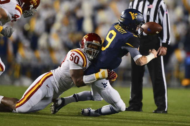Nov 30, 2013; Morgantown, WV, USA; Iowa State Cyclones defensive end Willie Scott (50) sacks and strips the ball from West Virginia Mountaineers quarterback Clint Trickett (9) during the second quarter at Milan Puskar Stadium. Mandatory Credit: Tommy Gilligan-USA TODAY Sports