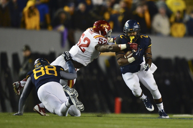 Nov 30, 2013; Morgantown, WV, USA; Iowa State Cyclones linebacker Jeremiah George (52) dives to tackle West Virginia Mountaineers running back Dreamius Smith (2) during the second quarter at Milan Puskar Stadium. Mandatory Credit: Tommy Gilligan-USA TODAY Sports