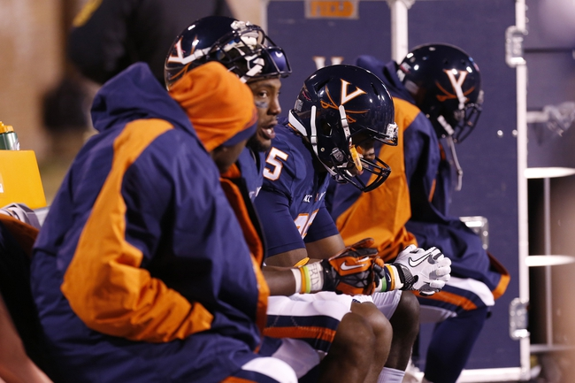 Nov 30, 2013; Charlottesville, VA, USA; Virginia Cavaliers players sit on the bench in the closing seconds of their game against the Virginia Tech Hokies at Scott Stadium. The Hokies won 16-6.  Mandatory Credit: Geoff Burke-USA TODAY Sports