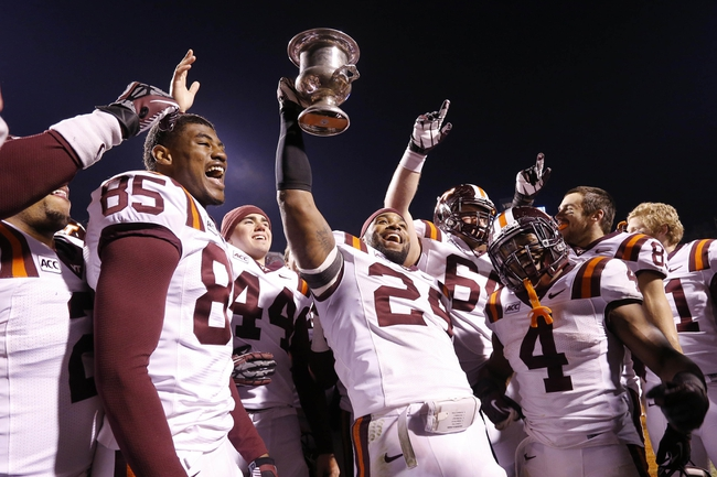 Nov 30, 2013; Charlottesville, VA, USA; Virginia Tech Hokies linebacker Tariq Edwards (24) holds the Commonwealth Cup while celebrating with teammates after their game against the Virginia Cavaliers at Scott Stadium. The Hokies won 16-6. Mandatory Credit: Geoff Burke-USA TODAY Sports
