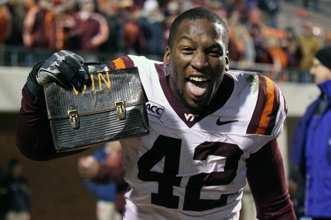 Nov 30, 2013; Charlottesville, VA, USA; Virginia Tech Hokies defensive end J.R. Collins (42) holds the victory lunch box after the game against the Virginia Cavaliers at Scott Stadium. The Hokies won 16-6. Mandatory Credit: Geoff Burke-USA TODAY Sports