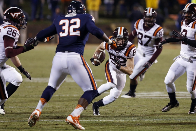 Nov 30, 2013; Charlottesville, VA, USA; Virginia Tech Hokies wide receiver Willie Byrn (82) runs with the ball as Virginia Cavaliers defensive end Mike Moore (32) defends in the third quarter at Scott Stadium. The Hokies won 16-6. Mandatory Credit: Geoff Burke-USA TODAY Sports