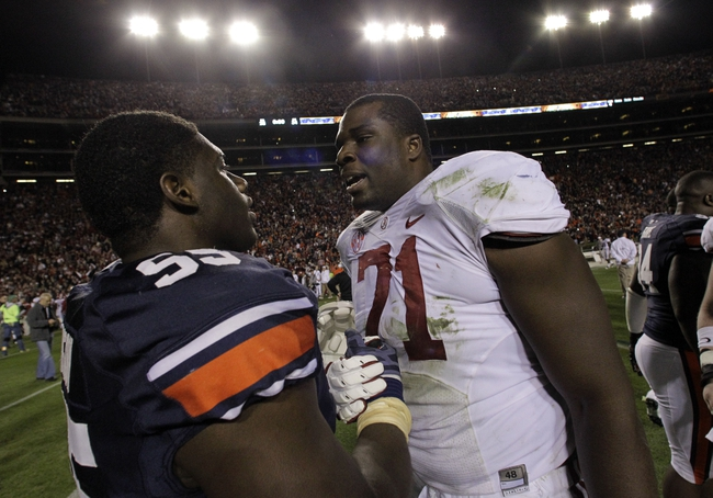 Nov 30, 2013; Auburn, AL, USA; Alabama Crimson Tide offensive linesman Cyrus Kouandjio (71) shakes hands with Auburn Tigers defensive end Carl Lawson (55) after the game at Jordan Hare Stadium. Auburn Tigers won 34-28. Mandatory Credit: John Reed-USA TODAY Sports