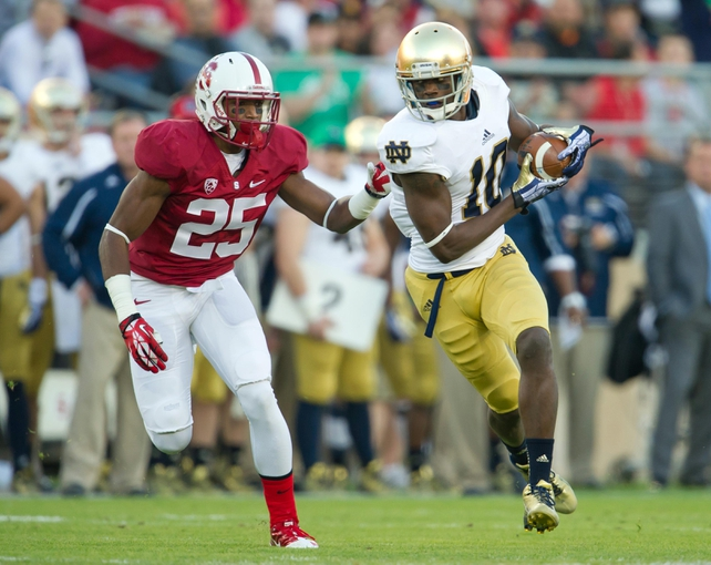 Nov 30, 2013; Stanford, CA, USA; Notre Dame Fighting Irish wide receiver DaVaris Daniels (10) carries the ball as Stanford Cardinal cornerback Alex Carter (25) defends in the first quarter at Stanford Stadium. Mandatory Credit: Matt Cashore-USA TODAY Sports