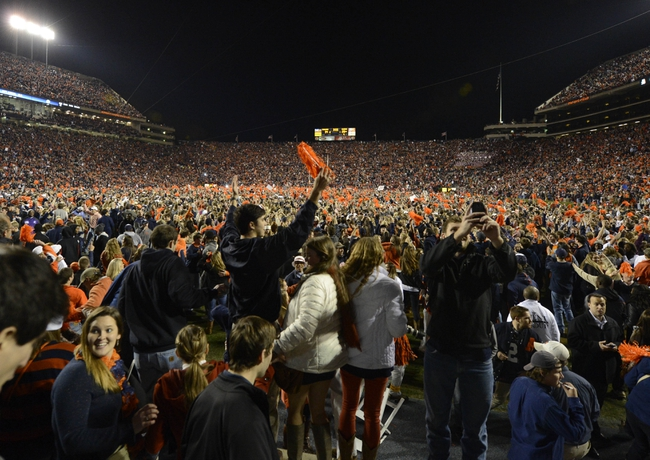 Nov 30, 2013; Auburn, AL, USA;  Auburn Tigers fans storm the field in celebration following their victory over the Alabama Crimson Tide 34-28 after a 100 yard return of a missed field goal by  cornerback Chris Davis (11) with no time left in the game at Jordan Hare Stadium. Mandatory Credit: RVR Photos-USA TODAY Sports