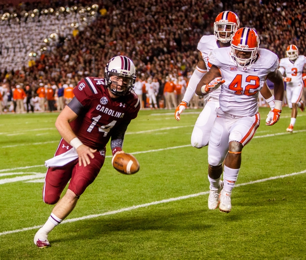 Nov 30, 2013; Columbia, SC, USA; South Carolina Gamecocks quarterback Connor Shaw (14) rushes for a touchdown as Clemson Tigers linebacker Stephone Anthony (42) pursues in the first quarter at Williams-Brice Stadium. Mandatory Credit: Jeff Blake-USA TODAY Sports
