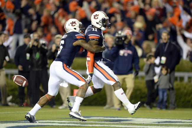 Nov 30, 2013; Auburn, AL, USA; Auburn Tigers cornerback Chris Davis (center) celebrates scoring a 100 yard touchdown on a missed field goal attempt with defensive back Jonathon Mincy (6) during the fourth quarter against the Alabama Crimson Tide at Jordan Hare Stadium. Auburn Tigers won 34-28. Mandatory Credit: John David Mercer-USA TODAY Sports