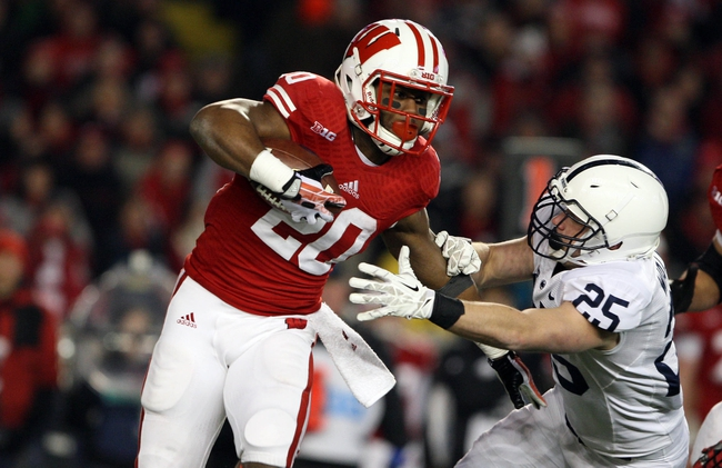 Nov 30, 2013; Madison, WI, USA; Wisconsin Badgers running back James White (20) rushes as Penn State Nittany Lions safety Von Walker (25) defends at Camp Randall Stadium. Penn State defeated Wisconsin 31-24. Mandatory Credit: Mary Langenfeld-USA TODAY Sports