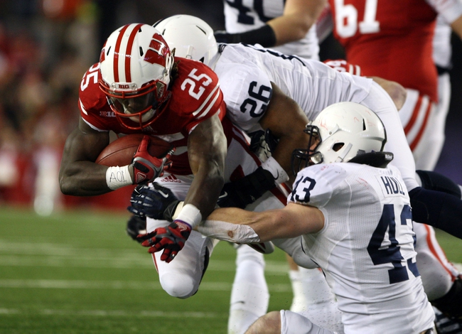 Nov 30, 2013; Madison, WI, USA; Wisconsin Badgers running back Melvin Gordon (25) rushes for a first down as Penn State Nittany Lions linebacker Brandon Bell (26) and Mike Hull (43) make the stop at Camp Randall Stadium. Penn State defeated Wisconsin 31-24. Mandatory Credit: Mary Langenfeld-USA TODAY Sports