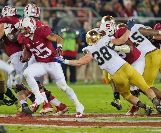 Nov 30, 2013; Stanford, CA, USA; Stanford Cardinal cornerback Alex Carter (25) carries the ball as Notre Dame Fighting Irish linebacker Joe Schmidt (38) attempts to tackle in the second quarter at Stanford Stadium. Mandatory Credit: Matt Cashore-USA TODAY Sports