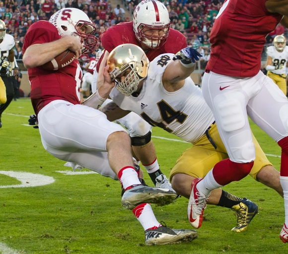 Nov 30, 2013; Stanford, CA, USA; Stanford Cardinal quarterback Kevin Hogan (8) is tackled by Notre Dame Fighting Irish linebacker Carlo Calabrese (44) in the first quarter at Stanford Stadium. Mandatory Credit: Matt Cashore-USA TODAY Sports