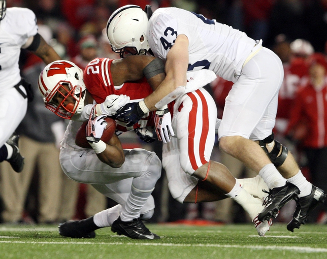Nov 30, 2013; Madison, WI, USA; Wisconsin Badgers running back James White is stopped by Penn State Nittany Lions linebacker Mike Hull (43) at Camp Randall Stadium. Penn State defeated Wisconsin 31-24. Mandatory Credit: Mary Langenfeld-USA TODAY Sports