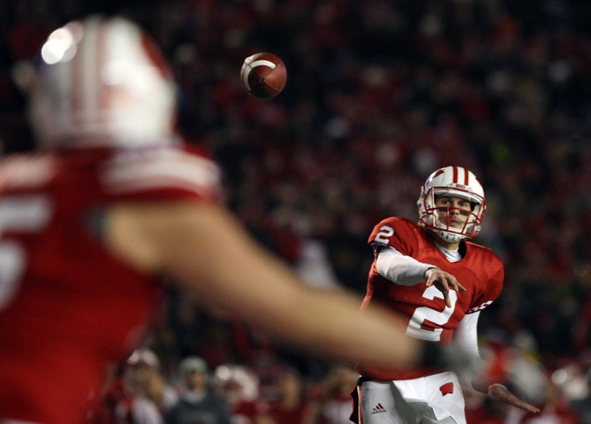 Nov 30, 2013; Madison, WI, USA; Wisconsin Badgers quarterback Joel Stave (2) throws a touchdown pass to tight end Brian Wozniak (foreground) as their team plays the Penn State Nittany Lions at Camp Randall Stadium. Penn State defeated Wisconsin 31-24. Mandatory Credit: Mary Langenfeld-USA TODAY Sports