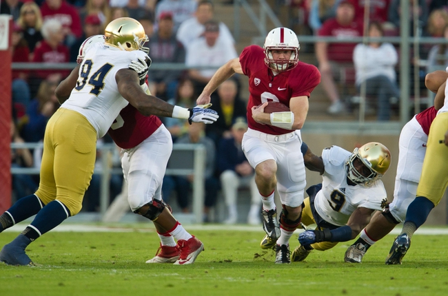 Nov 30, 2013; Stanford, CA, USA; Stanford Cardinal quarterback Kevin Hogan (8) carries the ball as Notre Dame Fighting Irish linebacker Jaylon Smith (9) attempts to tackle in the first quarter at Stanford Stadium. Mandatory Credit: Matt Cashore-USA TODAY Sports