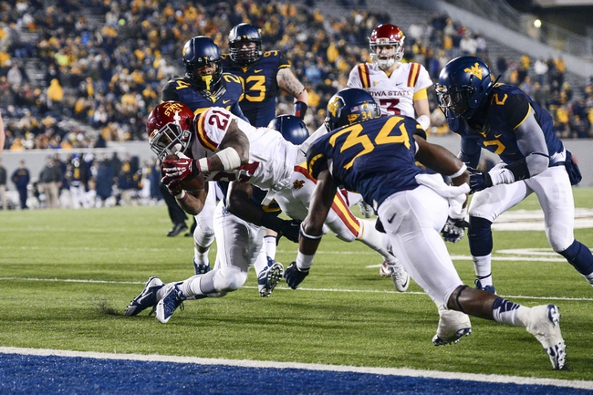 Nov 30, 2013; Morgantown, WV, USA; Iowa State Cyclones running back Shontrelle Johnson (21) dives through the West Virginia Mountaineers defense for a touchdown during the fourth quarter at Milan Puskar Stadium. Iowa State Cyclones defeated West Virginia Mountaineers 52-44 in the third overtime. Mandatory Credit: Tommy Gilligan-USA TODAY Sports