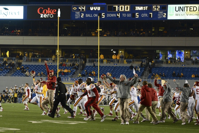Nov 30, 2013; Morgantown, WV, USA; Iowa State Cyclones team and coaches run on the field after stopping West Virginia Mountaineers offense in overtime  at Milan Puskar Stadium. Iowa State Cyclones defeated West Virginia Mountaineers 52-44 in the third overtime. Mandatory Credit: Tommy Gilligan-USA TODAY Sports