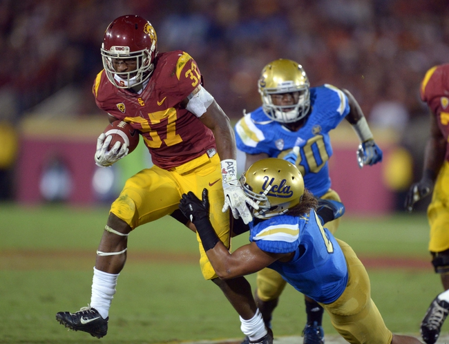 Nov 30, 2013; Los Angeles, CA, USA; Southern California Trojans tailback Javorious Allen (37) is defended by UCLA Bruins linebacker Eric Kendricks (6) at Los Angeles Memorial Coliseum. Mandatory Credit: Kirby Lee-USA TODAY Sports
