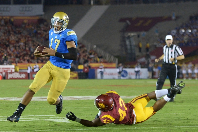 Nov 30, 2013; Los Angeles, CA, USA; UCLA Bruins quarterback Brett Hundley (17) eludes Southern California Trojans linebacker Devon Kenard (42) to score on a 4-yard touchdown run in the third quarter at Los Angeles Memorial Coliseum. Mandatory Credit: Kirby Lee-USA TODAY Sports