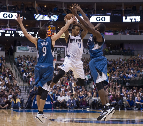 Nov 30, 2013; Dallas, TX, USA; Minnesota Timberwolves point guard Ricky Rubio (9) and power forward Luc Richard Mbah a Moute (12) defend against Dallas Mavericks shooting guard Monta Ellis (11) during the second half at the American Airlines Center. The Timberwolves defeated the Mavericks 112-106. Mandatory Credit: Jerome Miron-USA TODAY Sports