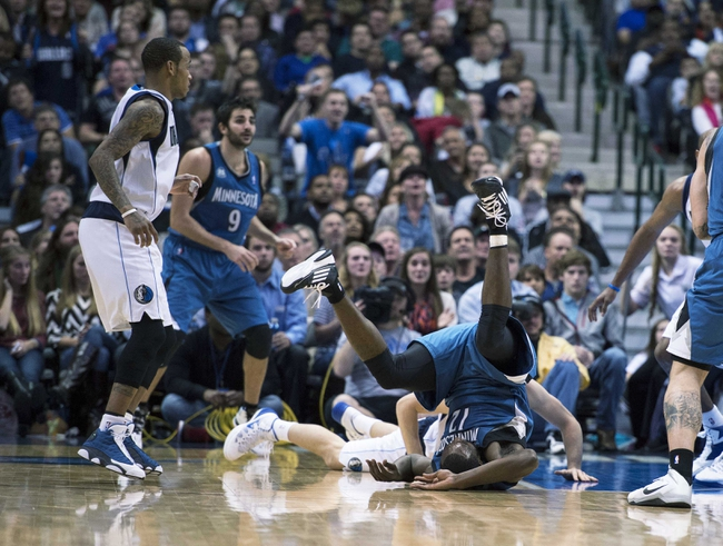 Nov 30, 2013; Dallas, TX, USA; Minnesota Timberwolves power forward Luc Richard Mbah a Moute (12) tumbles over Dallas Mavericks point guard Gal Mekel (33) while fighting for the ball during the second half at the American Airlines Center. The Timberwolves defeated the Mavericks 112-106. Mandatory Credit: Jerome Miron-USA TODAY Sports