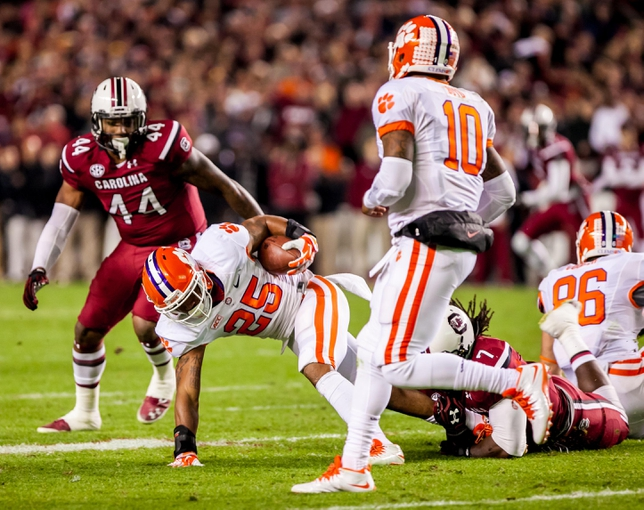 Nov 30, 2013; Columbia, SC, USA; Clemson Tigers running back Roderick McDowell (25) is brought down by South Carolina Gamecocks defensive end Jadeveon Clowney (7) in the second quarter at Williams-Brice Stadium. Mandatory Credit: Jeff Blake-USA TODAY Sports