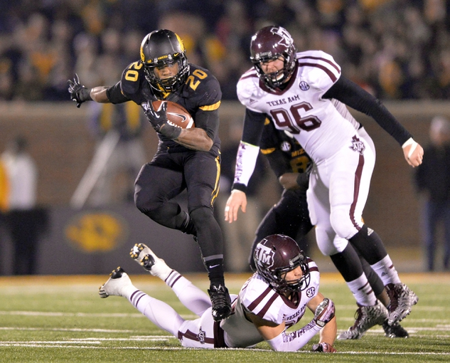 Nov 30, 2013; Columbia, MO, USA; Missouri Tigers running back Henry Josey (20) leaps over Texas A&M Aggies defender Clay Honeycutt (25) and rushes 57-yards for a touchdown during the second half at Faurot Field. Missouri defeated Texas A&M 28-21. Mandatory Credit: Peter G. Aiken-USA TODAY Sports