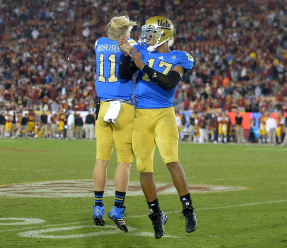 Nov 30, 2013; Los Angeles, CA, USA; UCLA Bruins quarterback Brett Hundley (17) celebrates with teammate Jerry Neuheisel (11) after a touchdown in the fourth quarter against the Southern California Trojans at Los Angeles Memorial Coliseum. Mandatory Credit: Kirby Lee-USA TODAY Sports