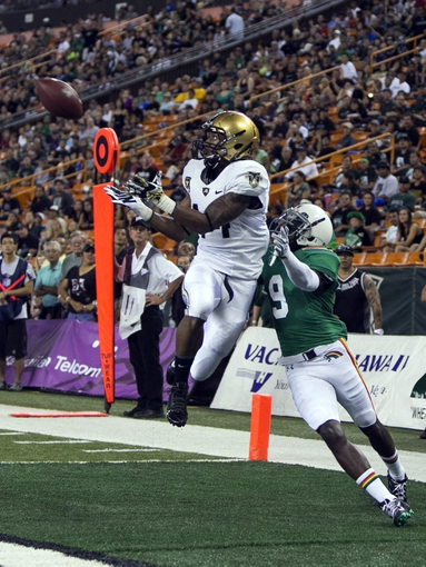 Nov 30, 2013; Honolulu, HI, USA; Army Black Knights defensive back Steven Johnson (14) pulls in an interception over Hawaii Warriors wide receiver Chris Gant (9) during the first quarter at Aloha Stadium. Mandatory Credit: Marco Garcia-USA TODAY Sports