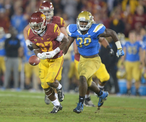 Nov 30, 2013; Los Angeles, CA, USA; Southern California Trojans tailback Javorious Allen (37) fumbles the ball as UCLA Bruins linebacker Myles Jack (30) defends at Los Angeles Memorial Coliseum. Mandatory Credit: Kirby Lee-USA TODAY Sports